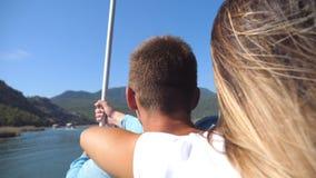 Поднимите задний взгляд молодых пар тратя время совместно на палубе парусника на солнечном дне Красивая девушка обнимая ее акции видеоматериалы