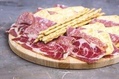 Поднос еды с очень вкусными частями салями отрезанной плиты ветчины и мяса шутих и ручек хлеба Стоковые Изображения RF