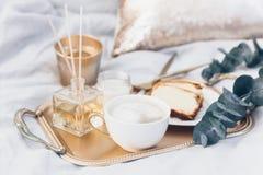 Поднос золота с кофе и евкалипт на чистых белых постельных принадлежностях Стоковое фото RF