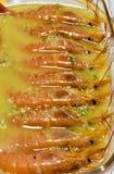 поднос стеклянное полного креветок сваренных с вкусным соусом чеснока, масла и петрушки готовых быть съеденным на таблице ( стоковая фотография