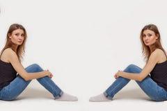 2 подобных молодой женщины сидят назад к сторонам изображения стоковая фотография