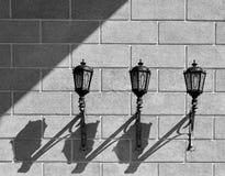 3 подобных фонарика прикрепленного к кирпичной стене бросая симметричные тени Стоковые Фото