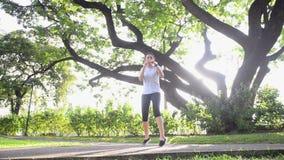 Подогрев азиатской женщины кладя в коробку в зеленом парке с большим деревом и солнечным светом сток-видео
