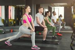 Подогрев группы фитнеса протягивая тренировать внутри помещения Стоковые Фото