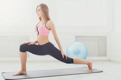 Подогрев женщины фитнеса протягивая тренировать внутри помещения Стоковые Изображения