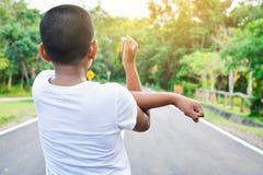 Подогрев мальчика перед бежать на дороге стоковое изображение