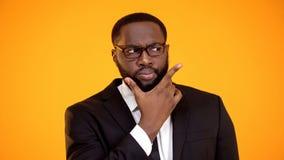 Подозрительный Афро-американский бизнесмен в стеклах принимая во внимание варианты, дилемма стоковое изображение