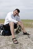 подоприте его пакет сидит утомленный путник Стоковая Фотография