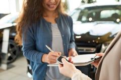 Подписывая контракт для нового автомобиля Стоковые Фотографии RF