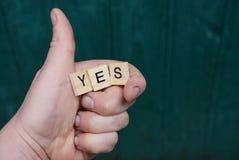 Подпишите да руку и деревянное слово на зеленой предпосылке Стоковая Фотография RF
