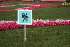 Подпишите доску на лужайке парка, спрашивая не выбрать вверх цветки Пожалуйста не шагните в траву стоковое изображение
