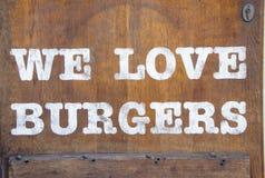 Подпишите ` мы любим ` бургеров на деревянной стене стоковая фотография rf