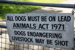 Подпишите на столбе строба говоря, что люди сдержали собаку на руководстве Стоковые Изображения RF