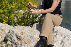 Подрежьте взгляд молодой взрослой бизнес-леди работая при таблетка сидя на крае скалы взморья стоковое изображение