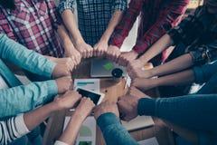 Подрезанная верхняя часть над фото взгляда высокого угла кулаков места партнерства партнеров профессионалов объезжает единство шо стоковая фотография