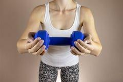 Подрезанная женщина в белой рубашке с dambbell в ее clase рук вверх Уменьшение концепции диеты и фитнеса стоковые фото
