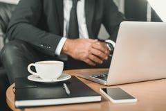 подрезанная съемка бизнесмена с компьтер-книжкой и кофе Стоковая Фотография RF