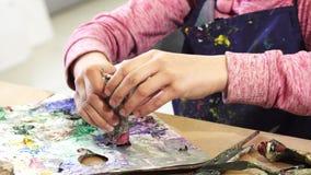 Подрезанная съемка девушки сжимая краску от трубки дальше к палитре стоковое изображение rf