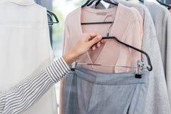 подрезанная съемка женщины выбирая одежды в выставочном зале Стоковое Фото
