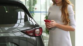 Подрезанная съемка женщины используя умный телефон на автосалоне видеоматериал