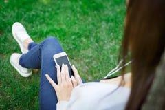Подрезанная съемка молодой девушки брюнет в наушниках занимаясь серфингом интернет на ее smartphone в парке Стоковые Фотографии RF