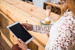 подрезанная съемка молодой женщины используя цифровую таблетку с пустым экраном пока сидящ в кафе Стоковые Фото