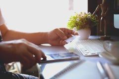 Подрезанная съемка мужских рук держа умный телефон с пустым экраном для онлайн покупок над столом Стоковое Изображение