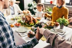 подрезанная съемка семьи держа руки и моля на благодарении раньше стоковые изображения rf