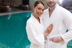 подрезанная съемка усмехаясь молодых пар в купальных халатах стоя близко бассейн стоковая фотография