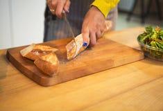 Подрезанная съемка хлеба багета вырезывания женщины на столешнице стоковая фотография rf