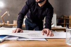 подрезанное изображение архитектора смотря светокопии на таблице Стоковая Фотография