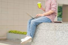 Подрезанное изображение бизнесмена работая вне офисного здания Стоковое фото RF