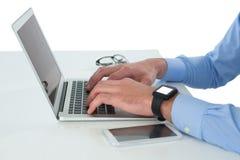 Подрезанное изображение бизнесмена работая на компьтер-книжке на таблице Стоковые Фото