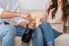 подрезанное изображение бутылки шампанского человека раскрывая пока его девушка стоковые фото