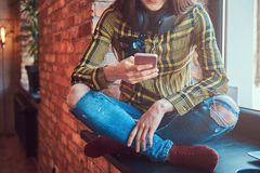 Подрезанное изображение девушки студента в музыке вскользь одежд слушая пока использующ smartphone пока сидящ на окне Стоковое Изображение RF