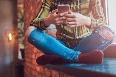 Подрезанное изображение девушки студента в музыке вскользь одежд слушая пока использующ smartphone пока сидящ на окне Стоковое Фото
