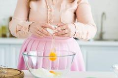 подрезанное изображение женщины добавляя яичко в шаре с мукой стоковое фото rf