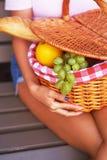 Подрезанное изображение женщины нося вскользь одежды держит корзину пикника пока сидящ на стенде в парке Стоковые Изображения RF