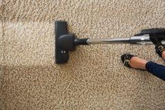 Подрезанное изображение ковра чистки женщины с пылесосом стоковое изображение