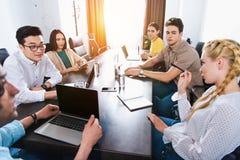 подрезанное изображение многокультурных деловых партнеров имея встречу на таблице с ноутбуками в современном стоковые изображения