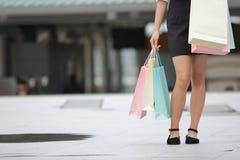 Подрезанное изображение рук молодой азиатской женщины держа хозяйственные сумки на улице города с космосом экземпляра Стоковое фото RF