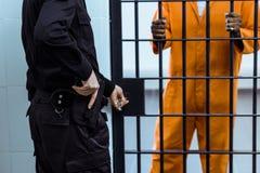 подрезанное изображение тюремного офицера кладя руку на оружие стоковое фото