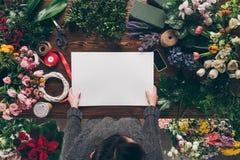 подрезанное изображение флориста держа пустой лист бумаги в руках выше стоковые фото