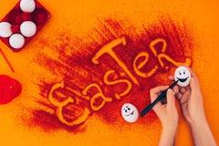 Подрезанное изображение smileys картины женщины на пасхальных яйцах Стоковое фото RF