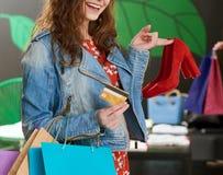 Подрезанное фото девушки держа пары красных ботинок в магазине Стоковое фото RF
