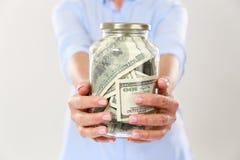 Подрезанное фото рук женщины держа стеклянный опарник с долларовой банкнотой Стоковая Фотография RF