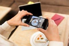 Подрезанное фото шляпы кавказской женщины нося фотографируя еду на сотовом телефоне стоковое изображение