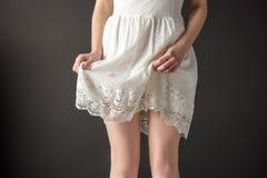 подрезанный взгляд девушки представляя в элегантном белом платье шнурка, стоковое изображение