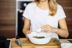 Подрезанный взгляд женщины вручает говядину вырезывания на разделочной доске Стоковые Изображения