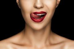 Подрезанный взгляд красивой женщины лижа губы с красной губной помадой Стоковые Фото